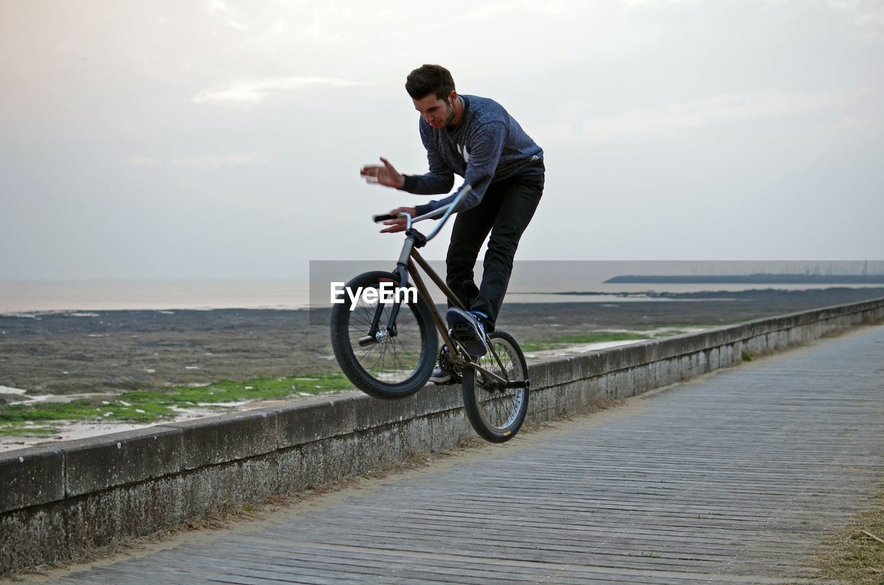 Young Man With Bicycle Standing On Retaining Wall