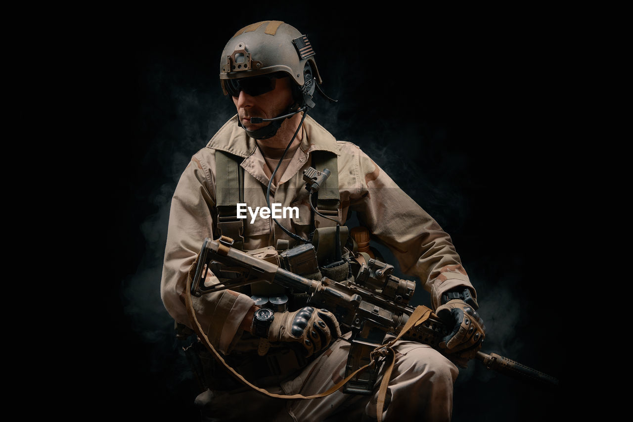 Man Wearing Helmet Holding Rifle Against Black Background