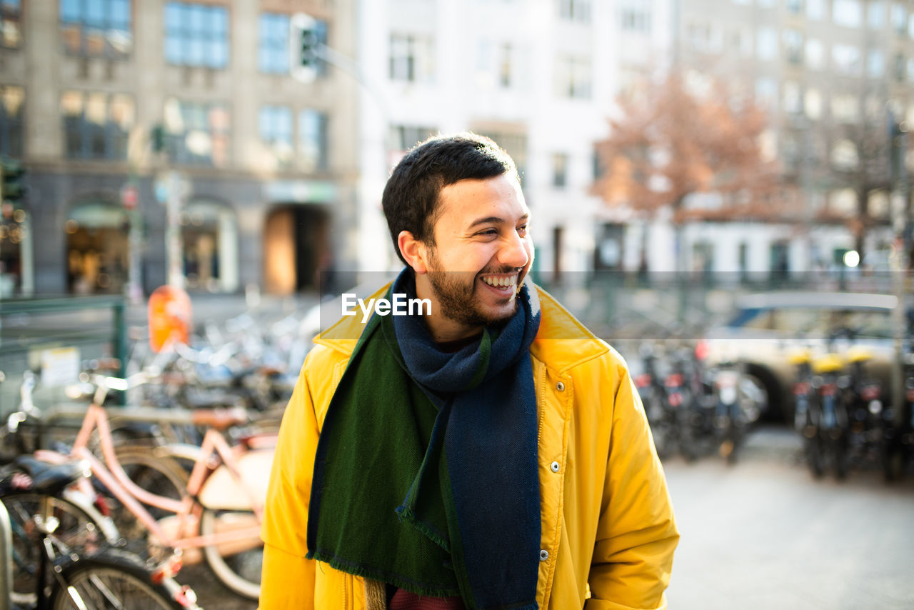 transportation, city, bicycle, one person, architecture, mode of transportation, building exterior, waist up, real people, smiling, front view, focus on foreground, clothing, land vehicle, yellow, built structure, happiness, street, lifestyles, outdoors
