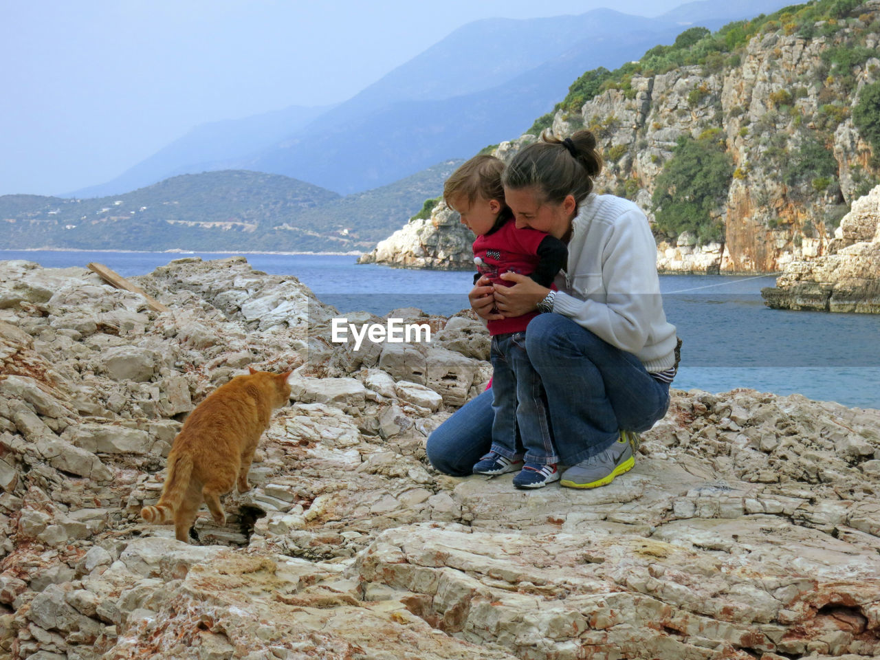Woman with daughter looking at cat on rock formation by sea