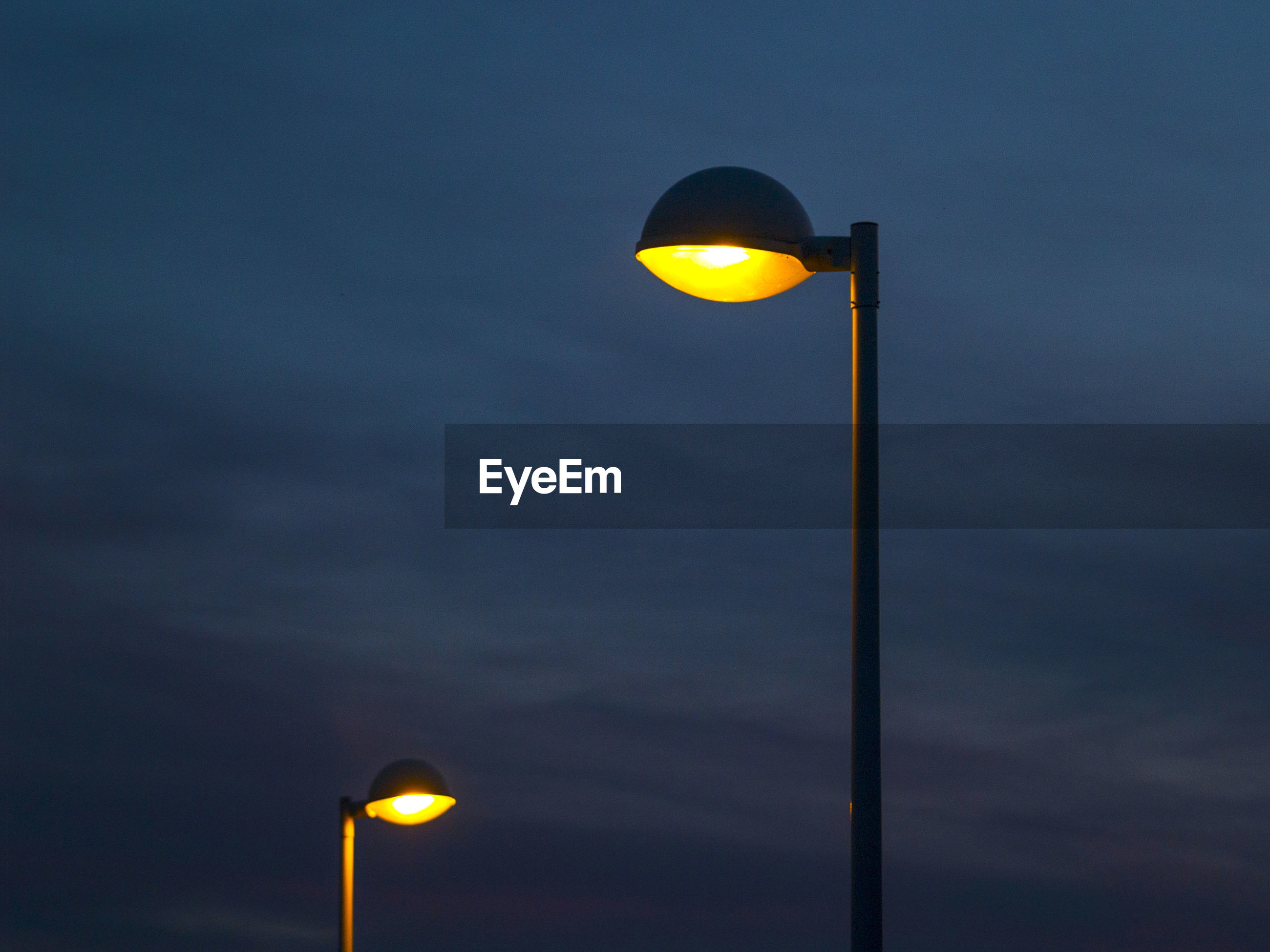 Low angle view of illuminated street lights against sky