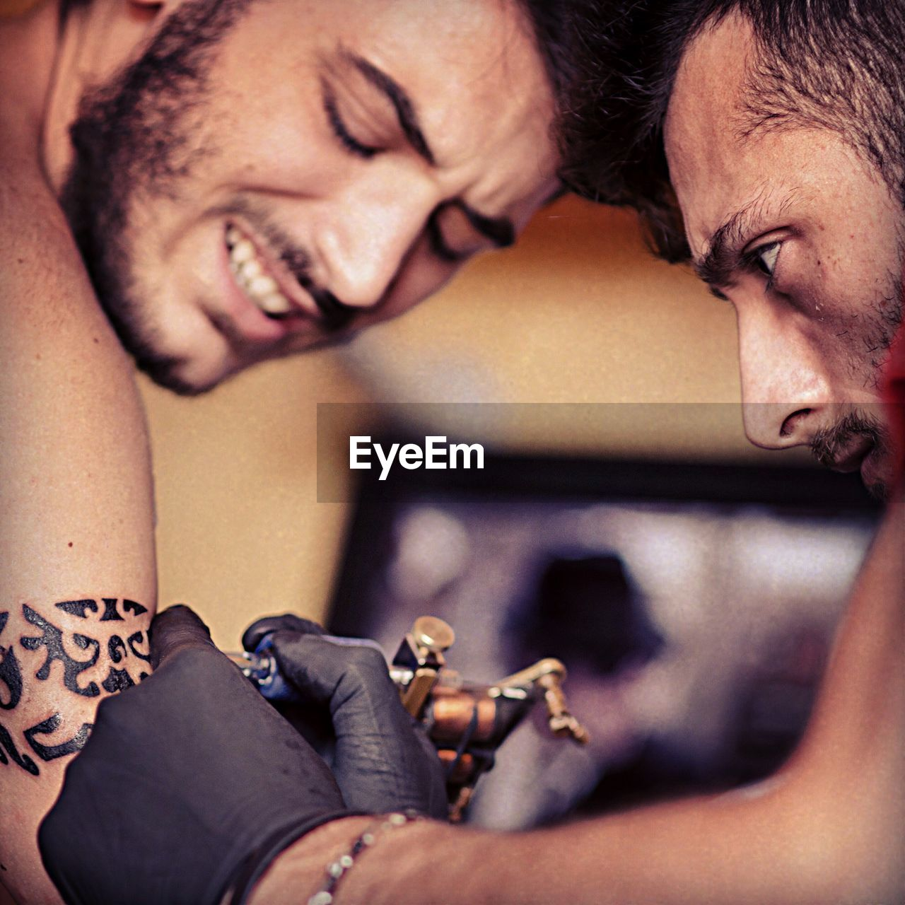 Close-Up Of Man Tattooing On Customer Arm
