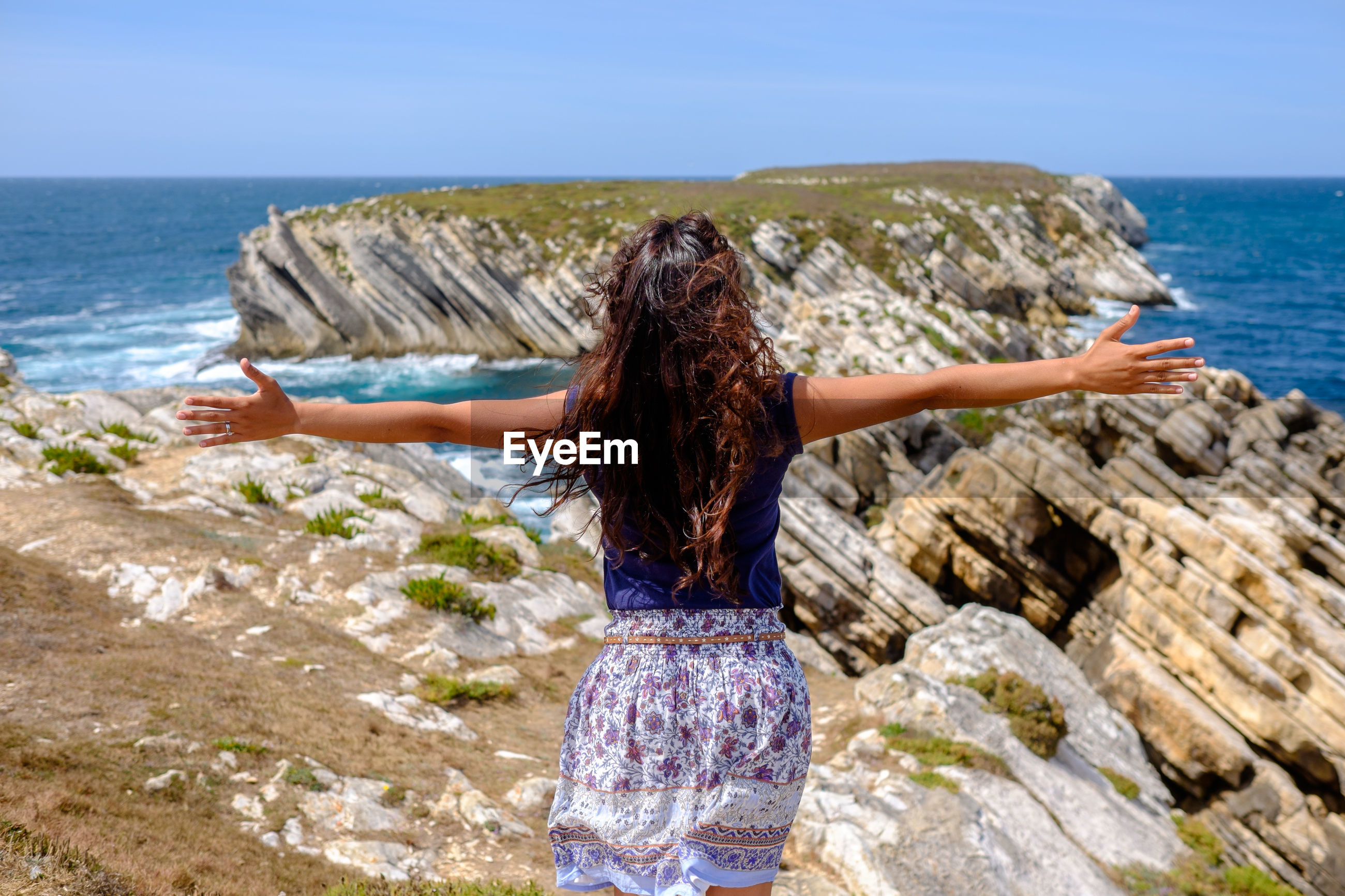 Rear view of woman standing on coast with her arms outstretched
