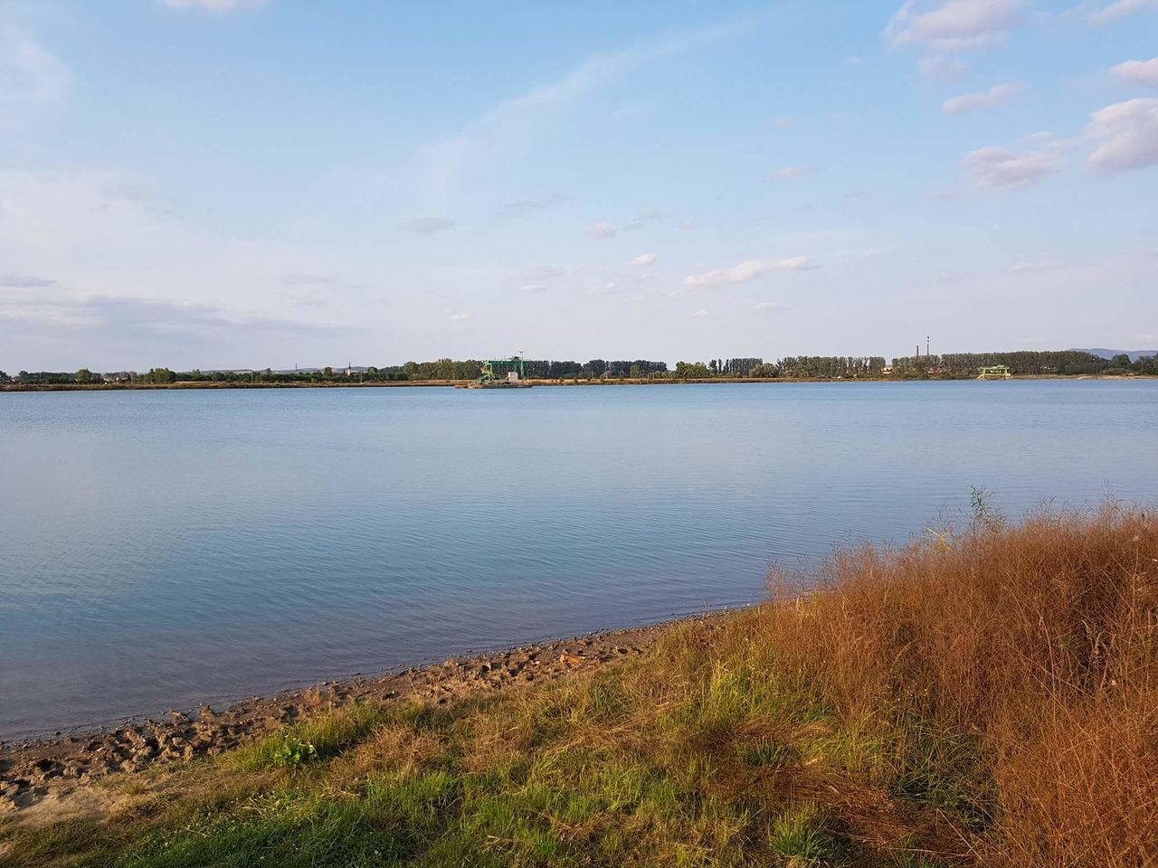 water, tranquil scene, nature, beauty in nature, tranquility, outdoors, scenics, grass, lake, day, sky, no people, landscape