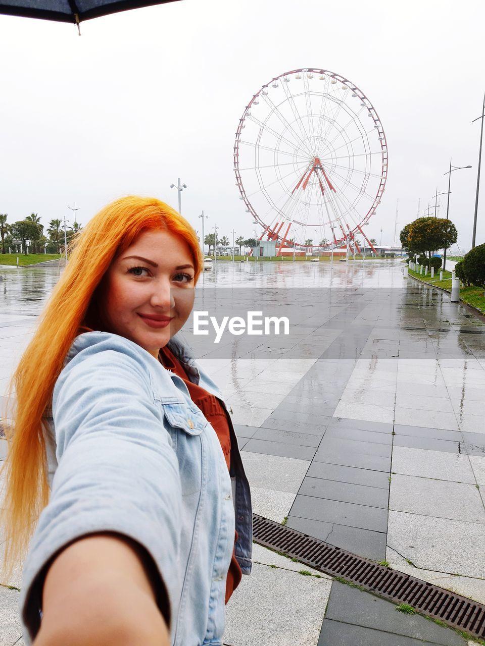 Portrait of smiling woman standing at amusement park