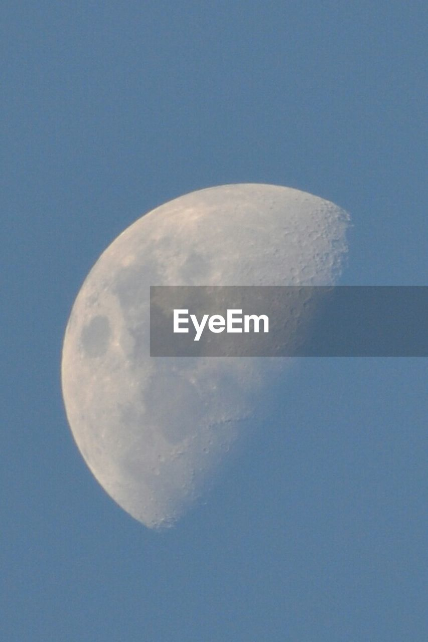 moon, moon surface, beauty in nature, astronomy, low angle view, planetary moon, nature, clear sky, tranquility, tranquil scene, half moon, night, sky, scenics, no people, space exploration, outdoors, blue, space, crescent, close-up