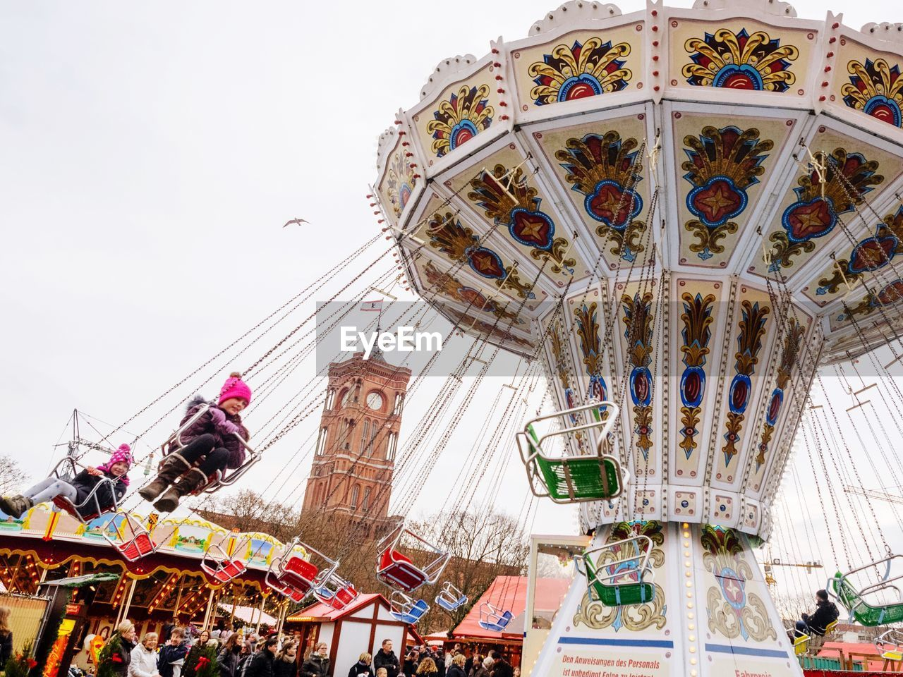 amusement park, arts culture and entertainment, amusement park ride, low angle view, leisure activity, carousel, enjoyment, built structure, day, merry-go-round, large group of people, outdoors, clear sky, real people, architecture, sky, people