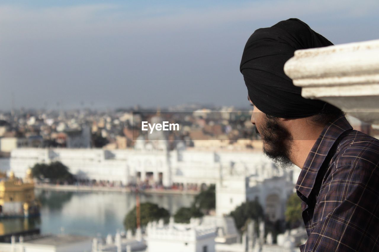 Side view of young man looking at cityscape