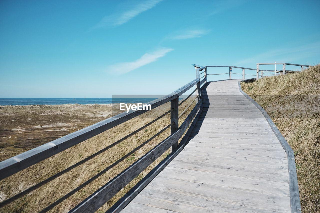Boardwalk Leading Towards Sea Against Clear Sky