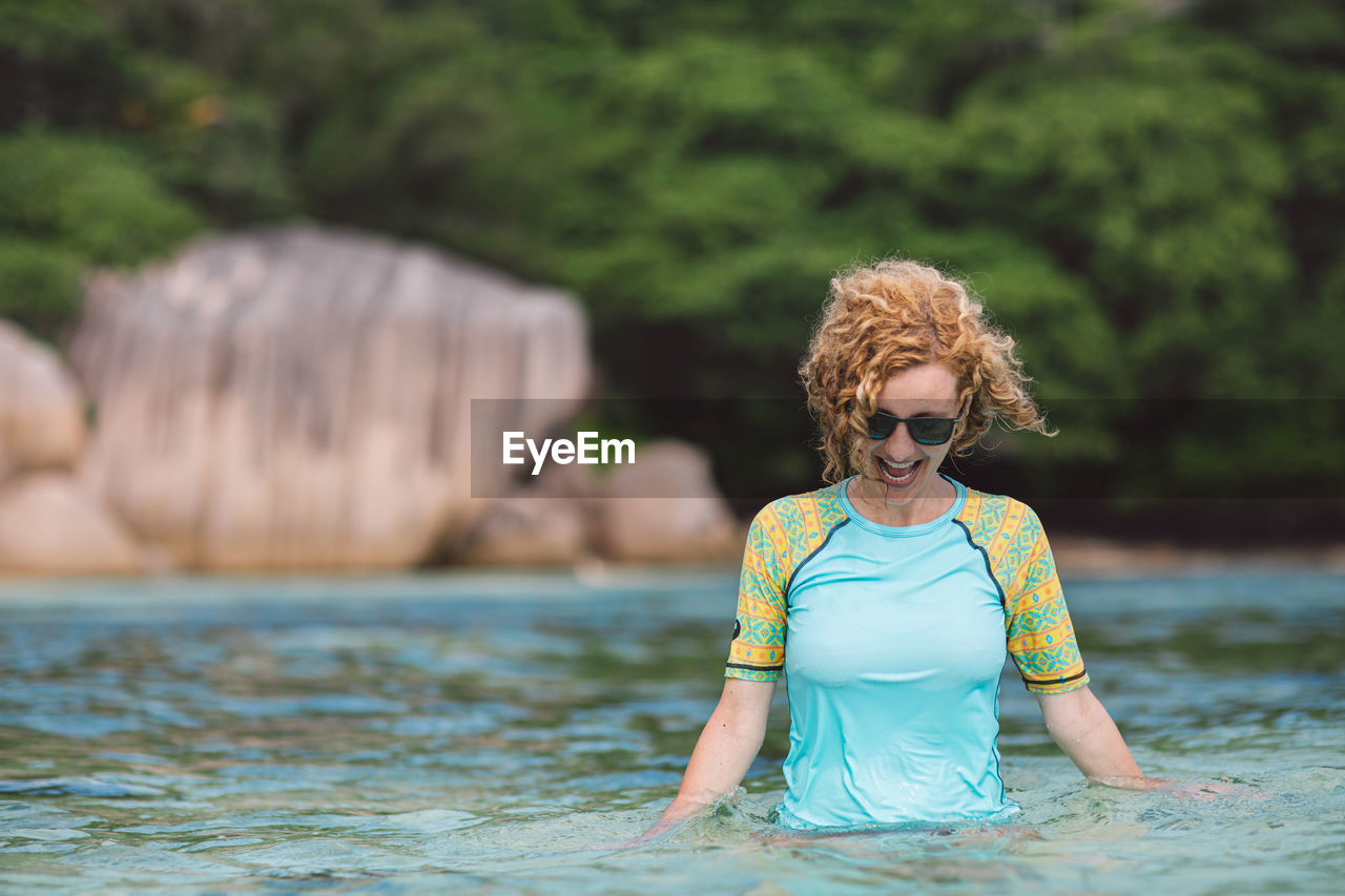 water, one person, leisure activity, real people, lifestyles, curly hair, focus on foreground, nature, day, women, adult, front view, females, short hair, land, casual clothing, young adult, hairstyle, outdoors