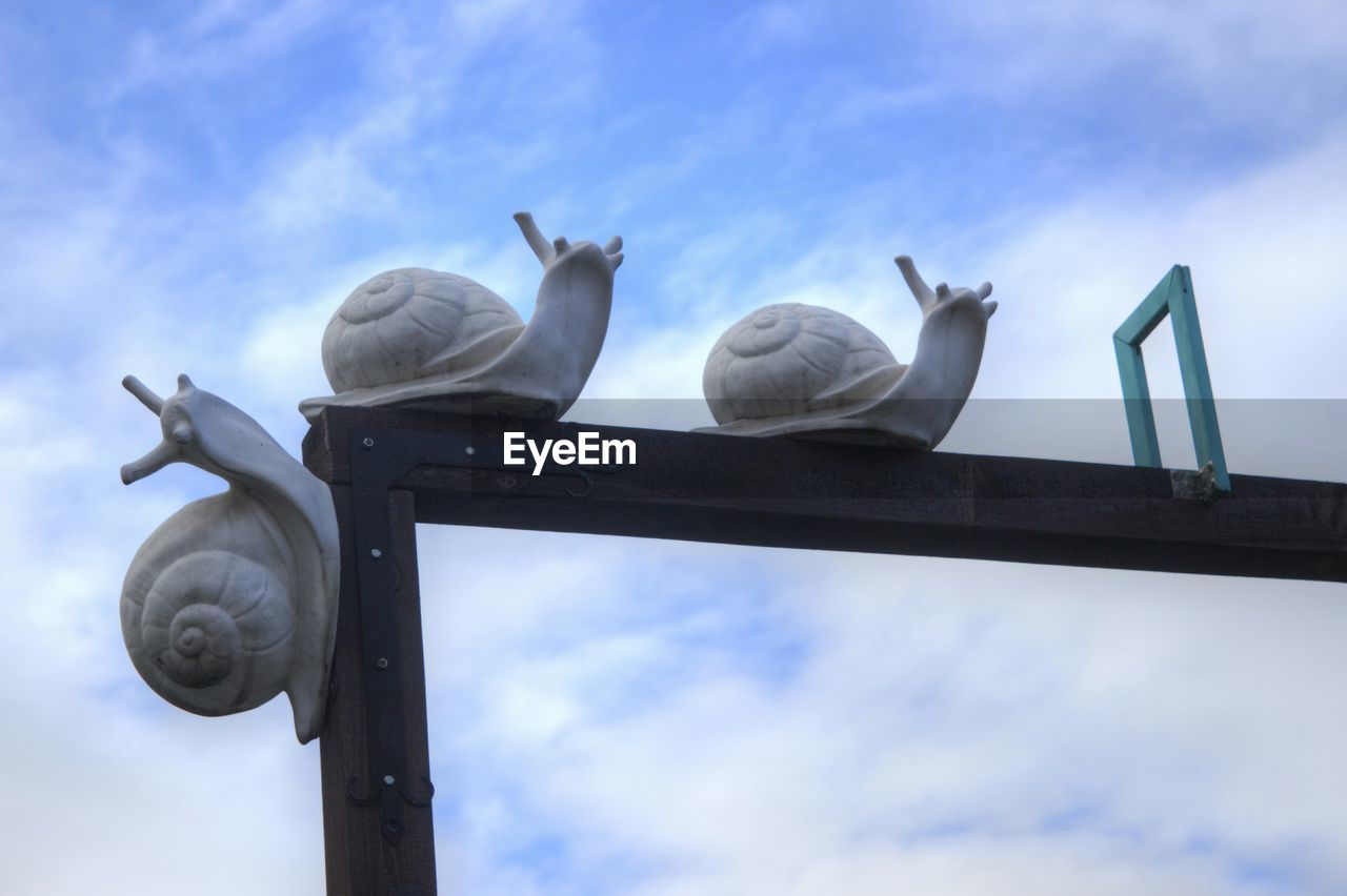 Low Angle View Of Snail Statues On Structure Against Sky