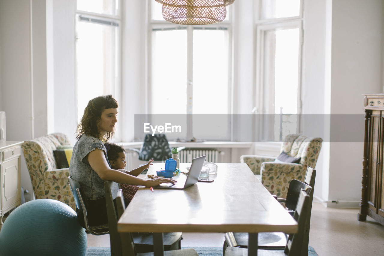 table, sitting, indoors, three quarter length, one person, real people, casual clothing, cup, lifestyles, window, day, chair, adult, mug, drink, food and drink, home interior, seat, furniture, hairstyle