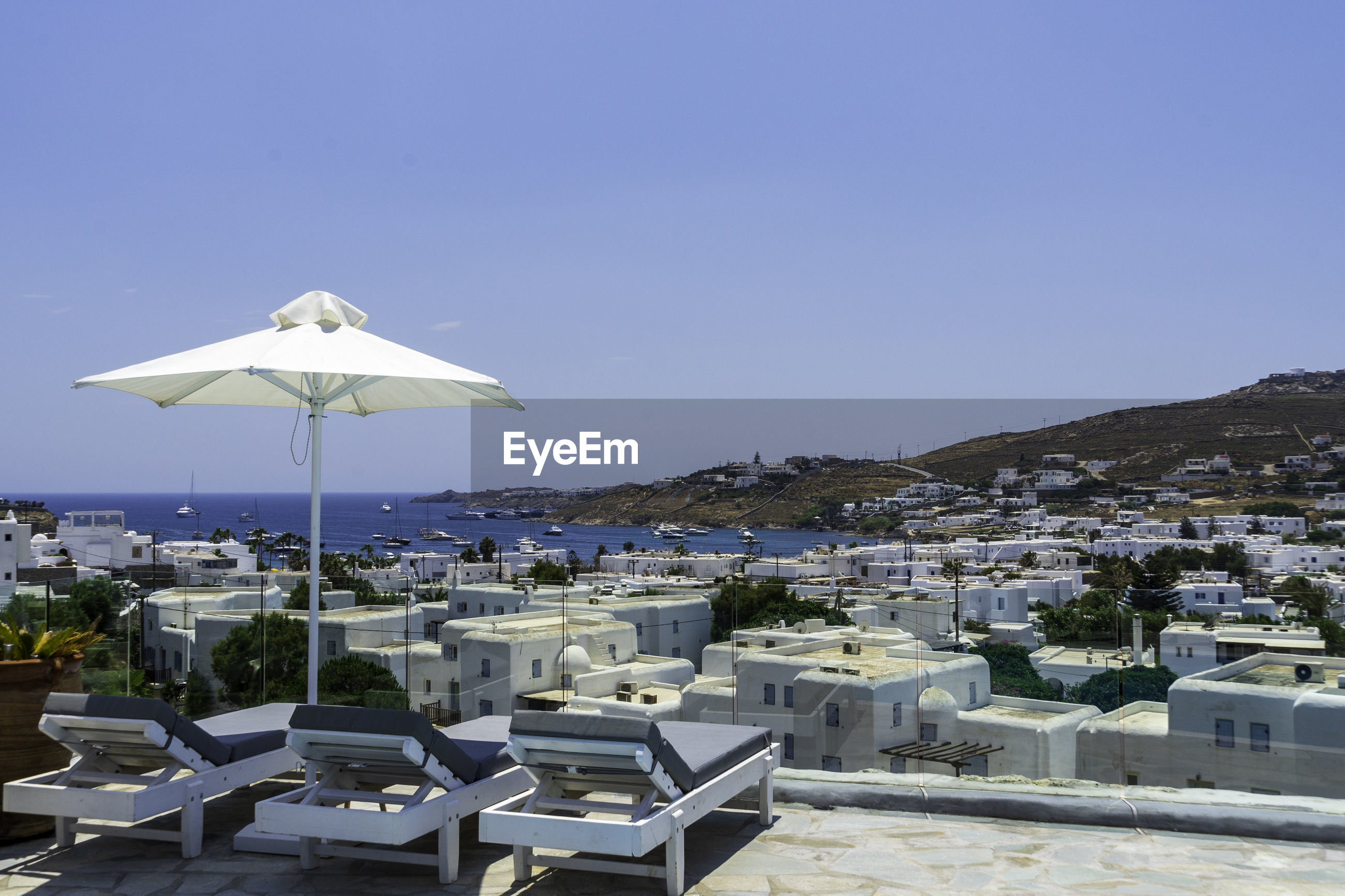 Scenic view of sea and buildings in mykonos against clear blue sky