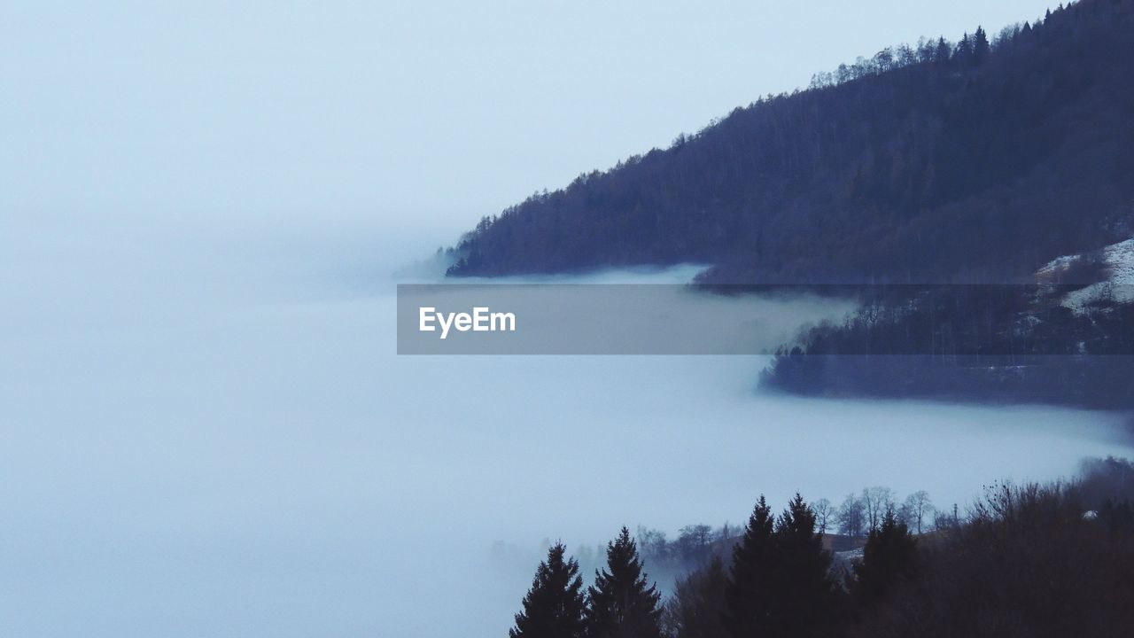 Scenic View Of Lake By Mountains In Foggy Weather