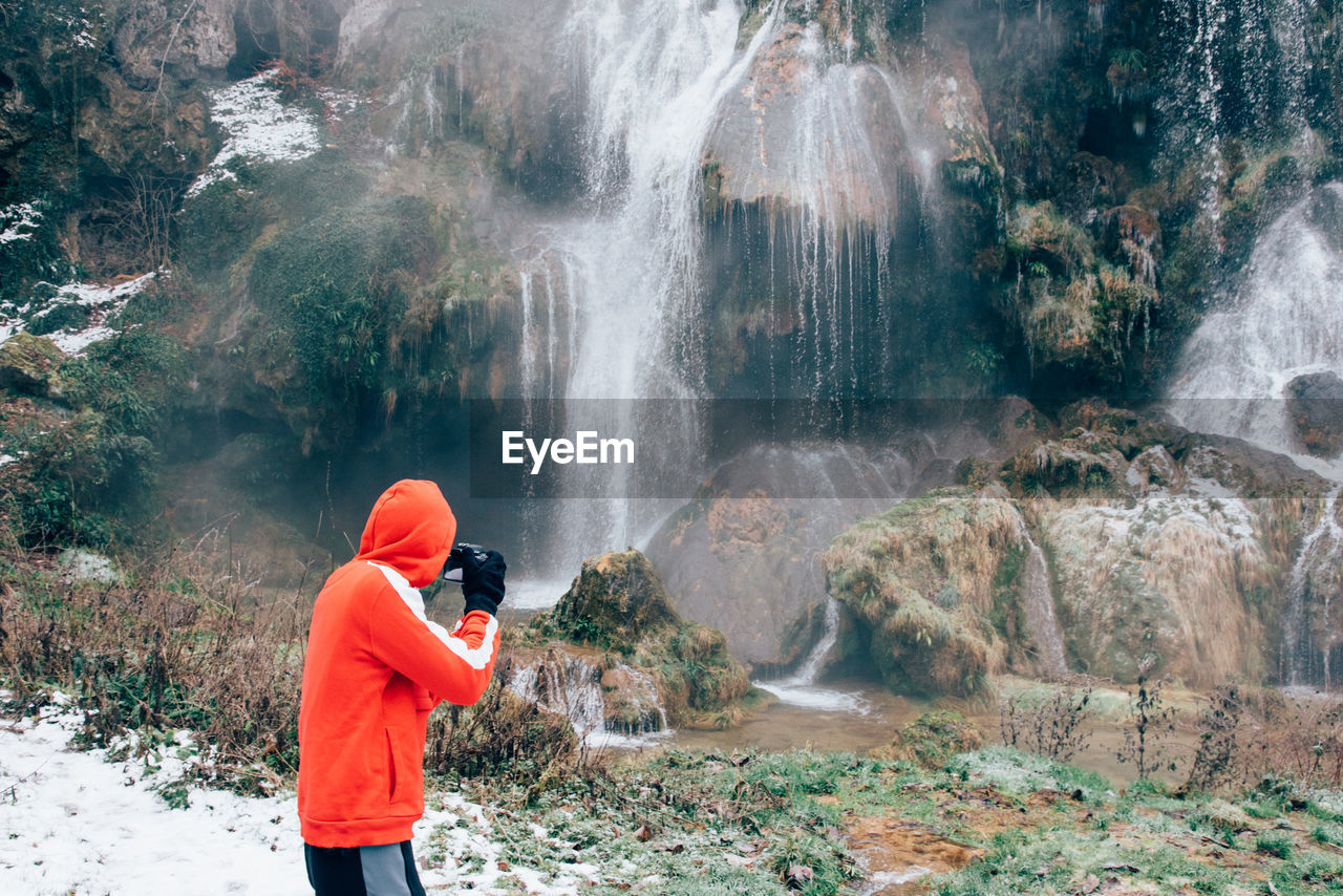 Side View Of Hiker Photographing Waterfall