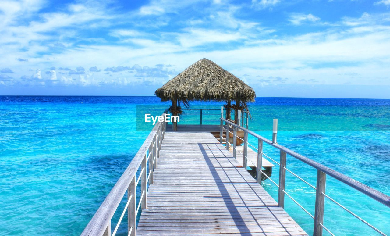 water, sea, sky, horizon, horizon over water, thatched roof, cloud - sky, blue, beauty in nature, scenics - nature, nature, day, tranquility, railing, no people, architecture, tranquil scene, roof, idyllic, outdoors, turquoise colored