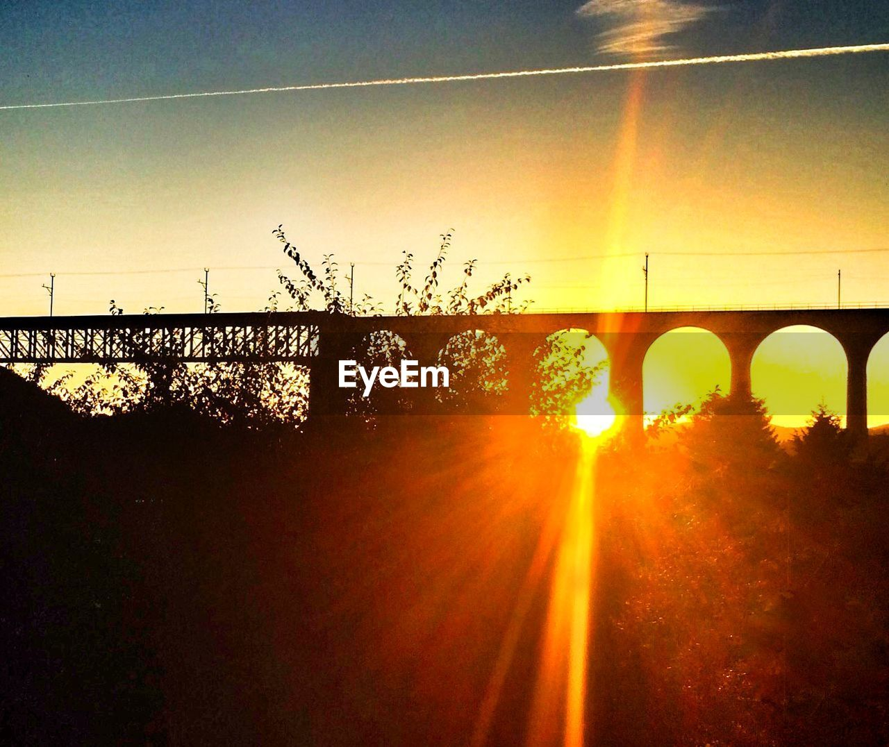 bridge - man made structure, connection, sunset, sun, transportation, lens flare, sunbeam, sunlight, nature, silhouette, arch, built structure, architecture, sky, outdoors, no people, tree, bridge, clear sky, growth, day