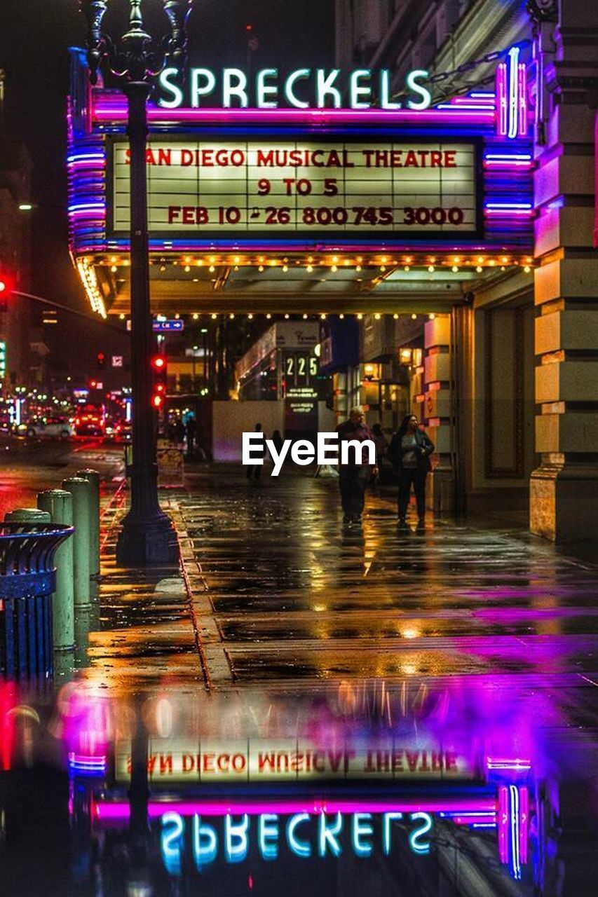 illuminated, western script, text, night, neon, nightlife, building exterior, communication, architecture, built structure, real people, walking, large group of people, city, outdoors, lifestyles, men, multi colored, people, adult