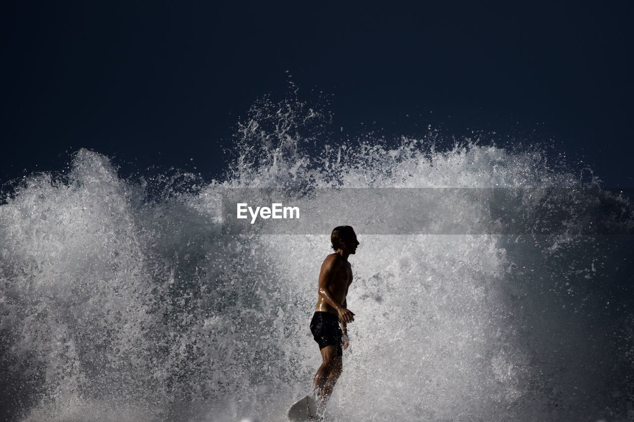 motion, water, one person, splashing, sea, sport, nature, wave, power, young adult, aquatic sport, men, power in nature, copy space, beauty in nature, vitality, strength, surfing, outdoors, black background, conquering adversity, breaking