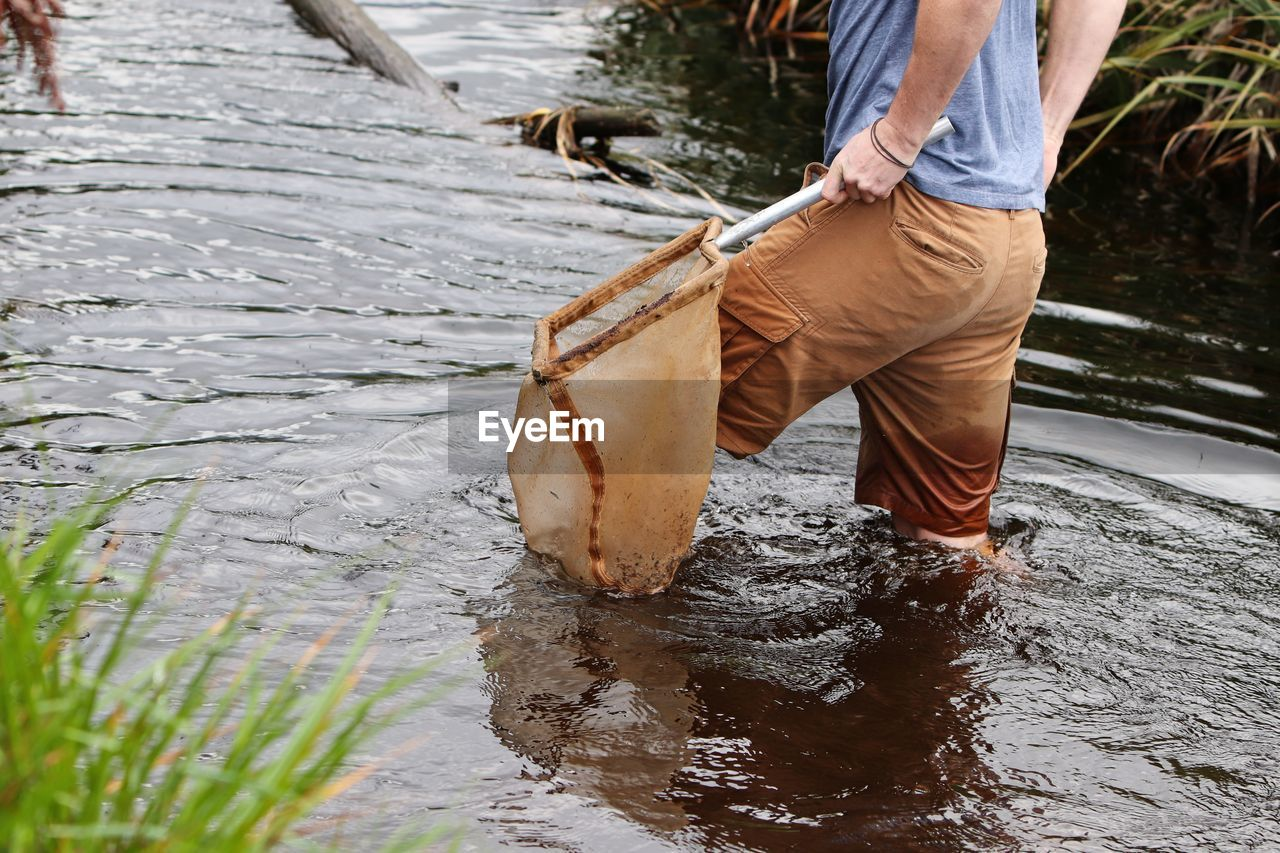 LOW SECTION OF MAN STANDING ON RIVER