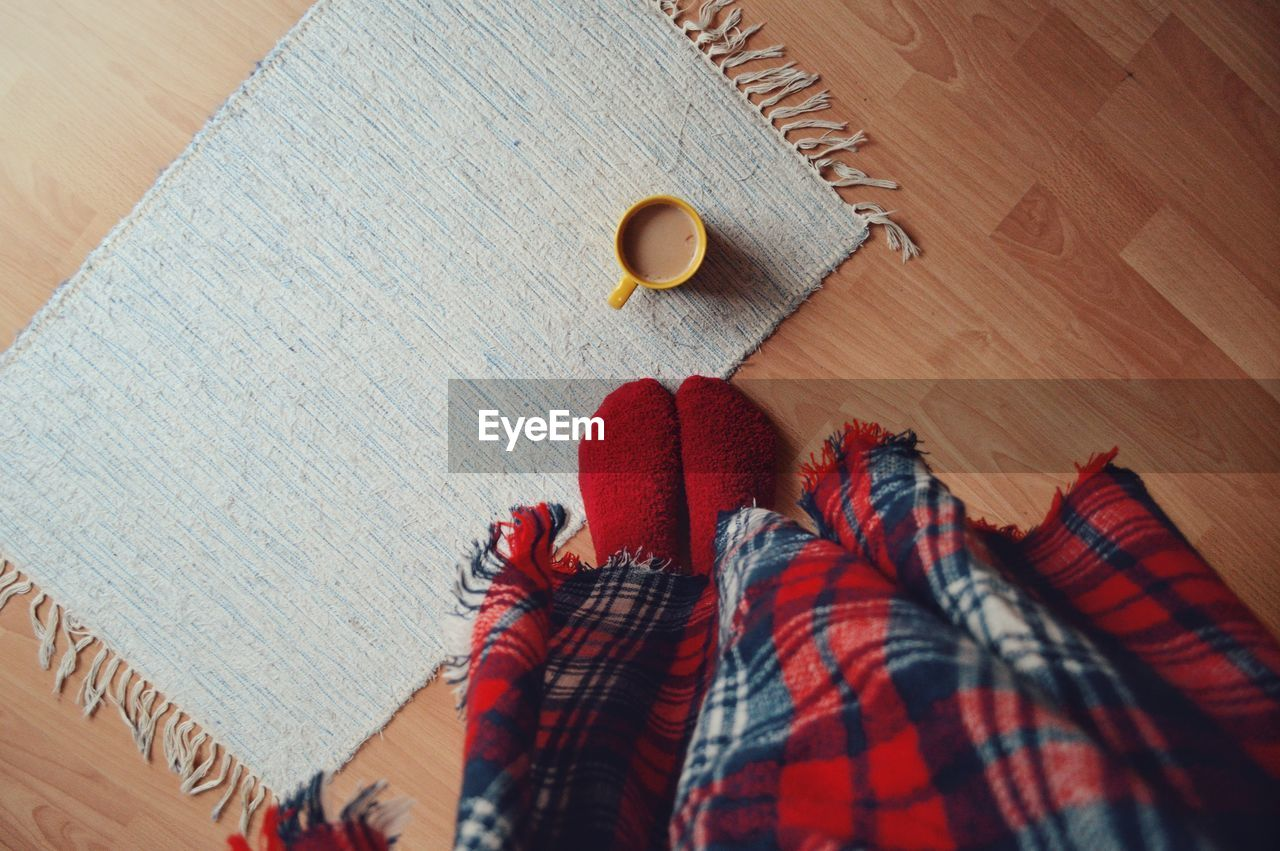 Low Section Of Woman With Coffee Mug On Hardwood Floor At Home