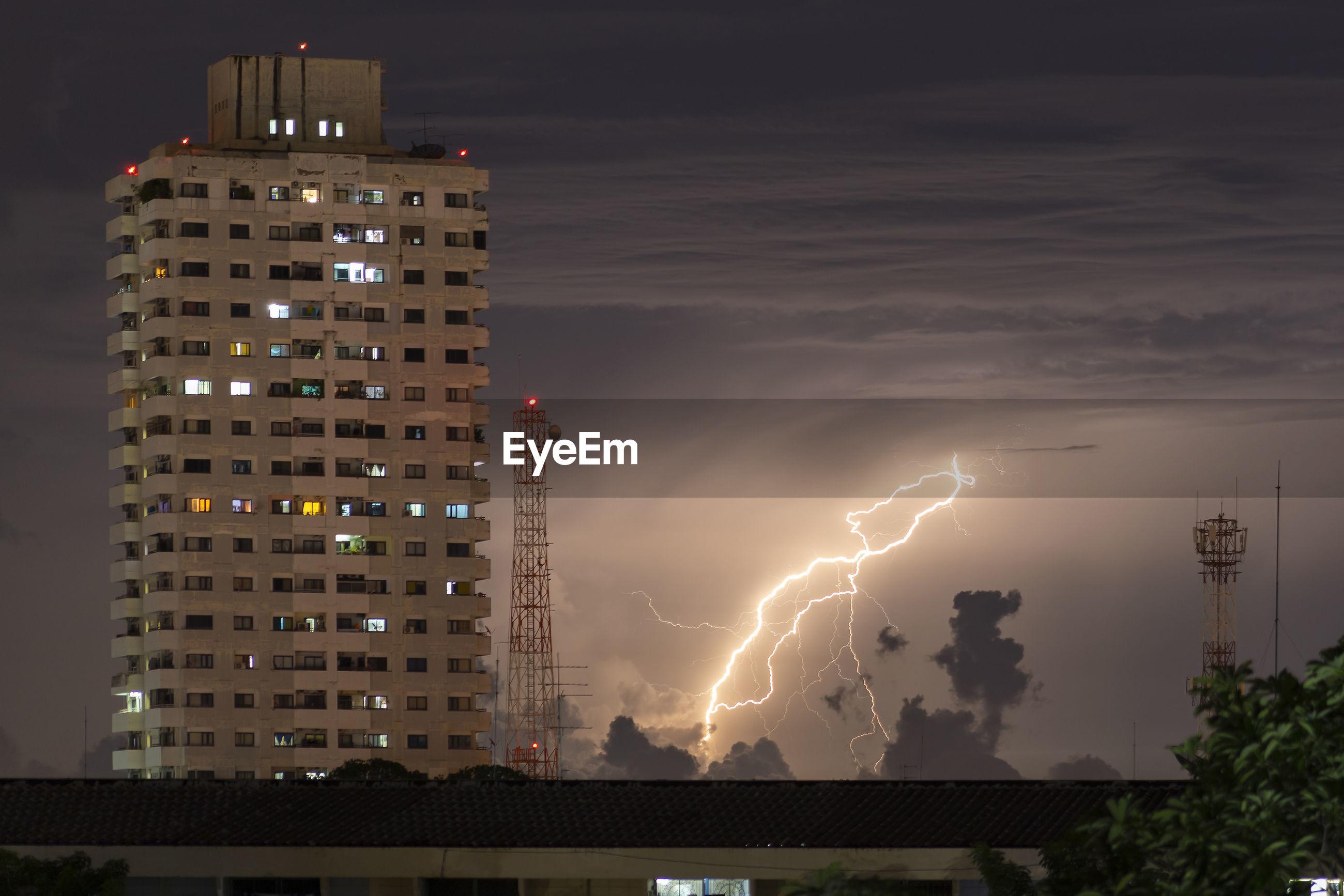 PANORAMIC SHOT OF ILLUMINATED BUILDINGS AGAINST SKY