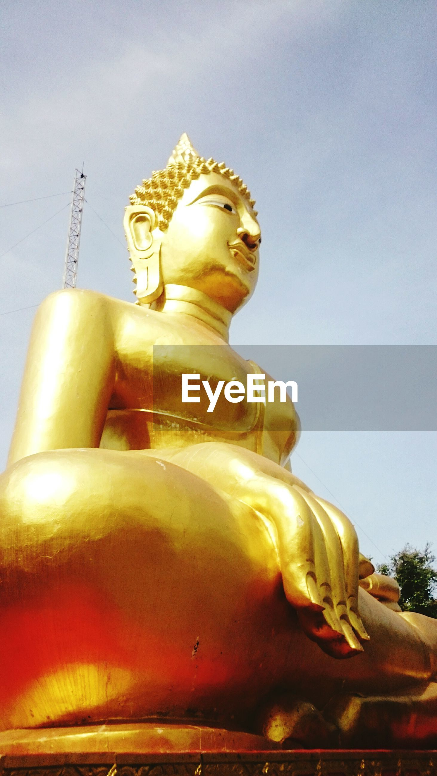 Low angle view of large golden buddha statue against sky