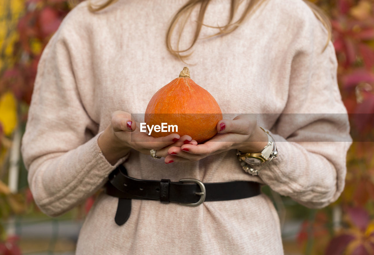 midsection, one person, focus on foreground, holding, fruit, food and drink, food, front view, wellbeing, healthy eating, standing, close-up, day, casual clothing, freshness, orange color, adult, autumn, healthy lifestyle, orange