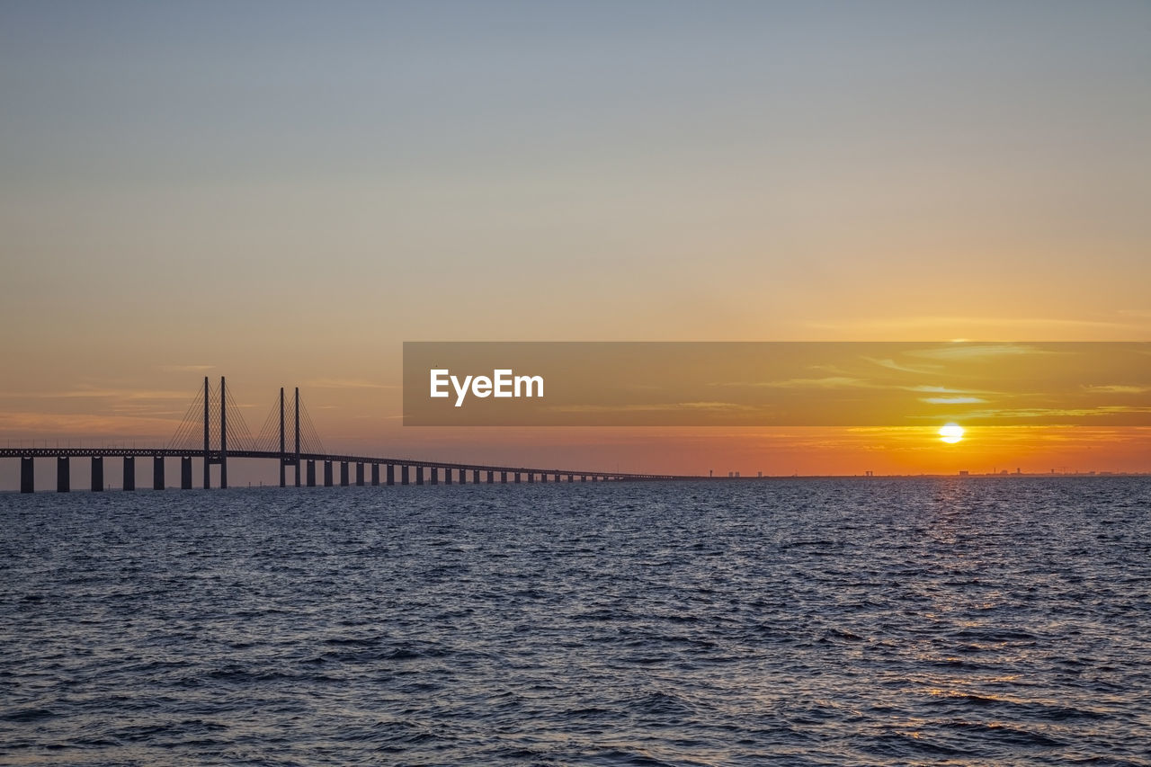 sunset, sky, water, sea, scenics - nature, beauty in nature, waterfront, orange color, tranquil scene, tranquility, no people, nature, idyllic, horizon over water, built structure, architecture, non-urban scene, cloud - sky, sun, bridge - man made structure, outdoors, wooden post