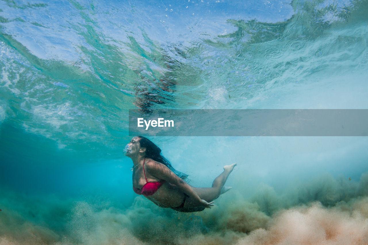 Woman wearing bikini while swimming in sea