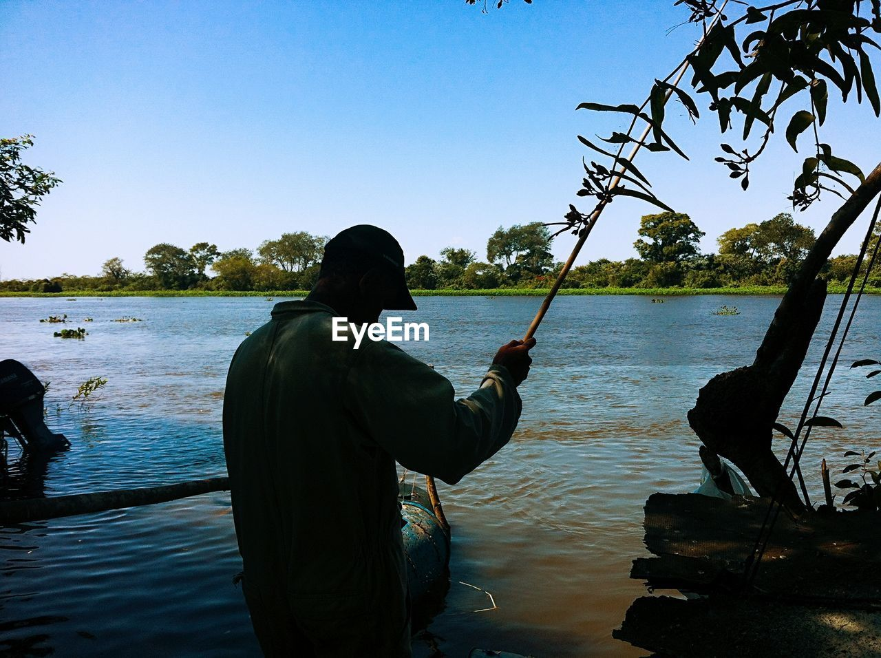 Rear view of man holding fishing road while standing in river against sky