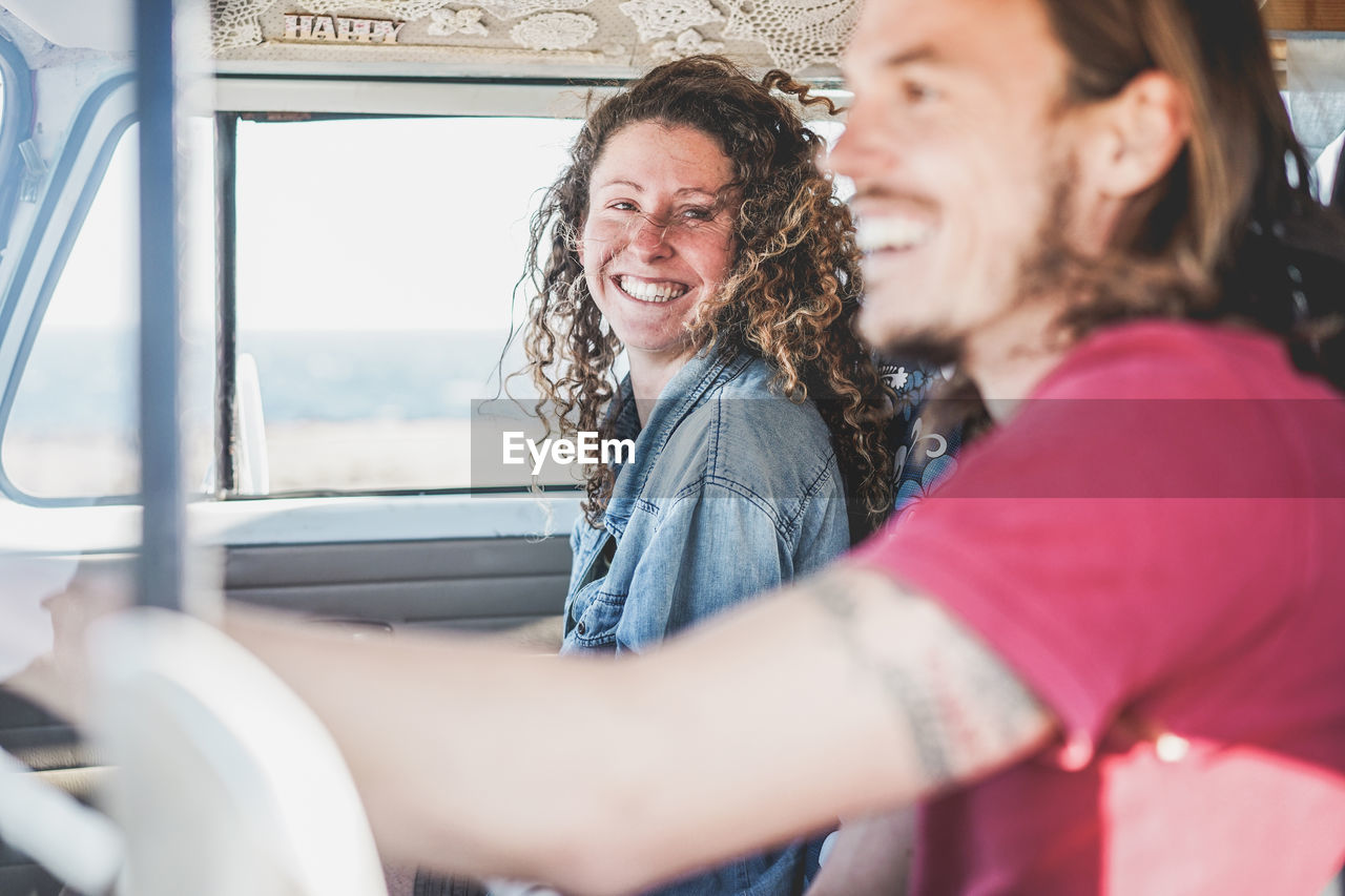 Cheerful friends traveling in vehicle