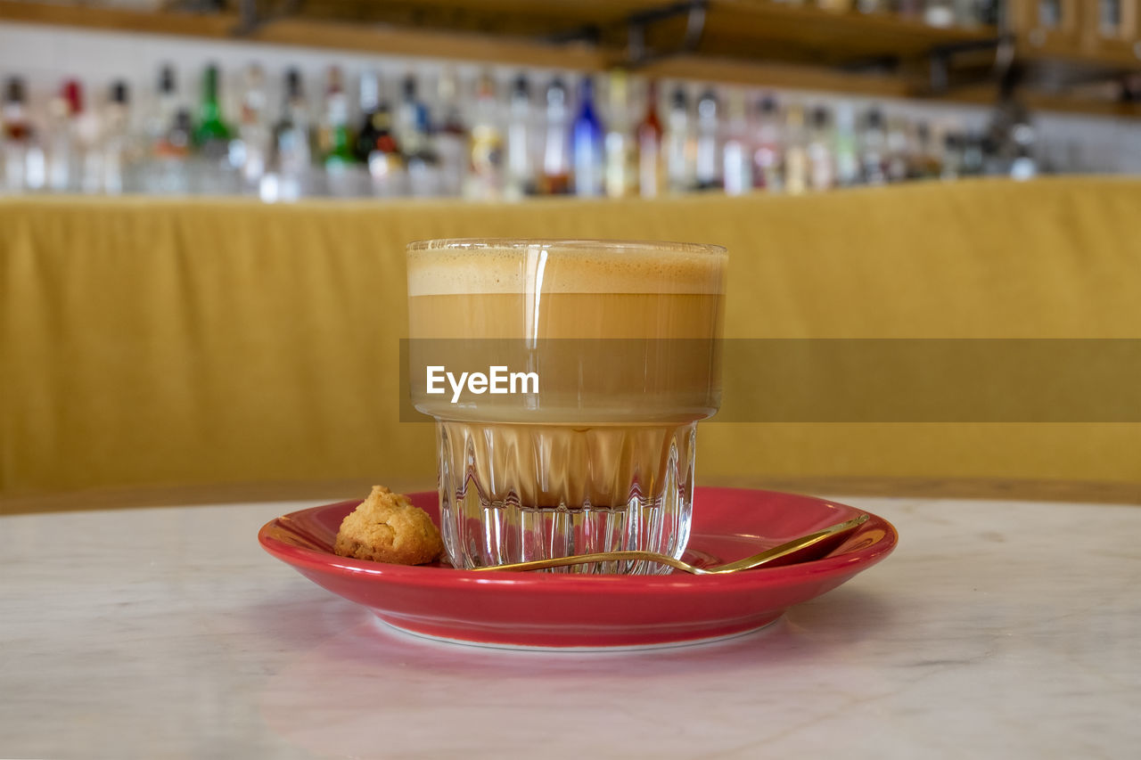 CLOSE-UP OF COFFEE WITH GLASS ON TABLE