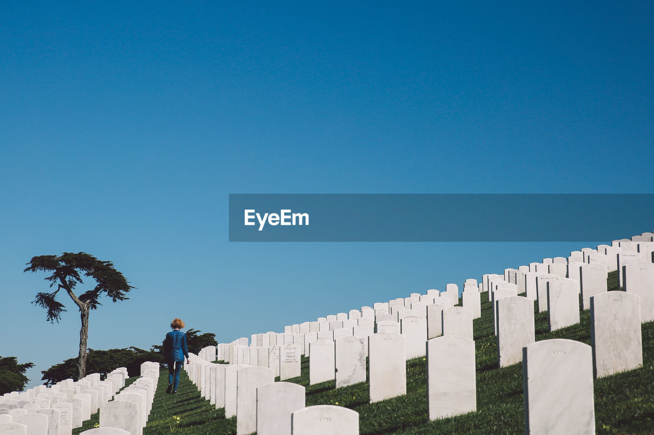 Rear View Of Woman Walking Amidst Graves At Cemetery