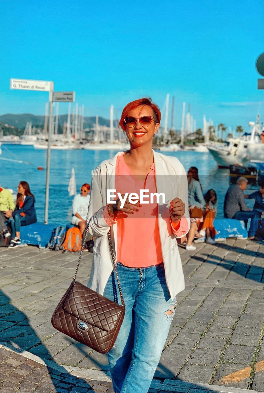 Portrait of smiling woman wearing sunglasses standing at harbor