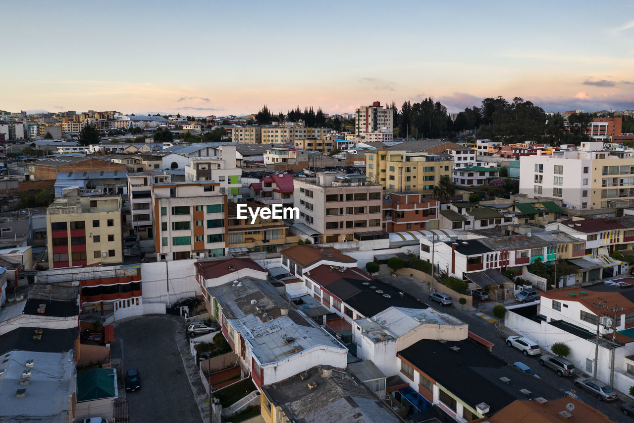 architecture, built structure, city, building exterior, building, residential district, sky, high angle view, cityscape, sunset, nature, no people, outdoors, cloud - sky, mode of transportation, transportation, car, land vehicle, apartment, townscape, settlement