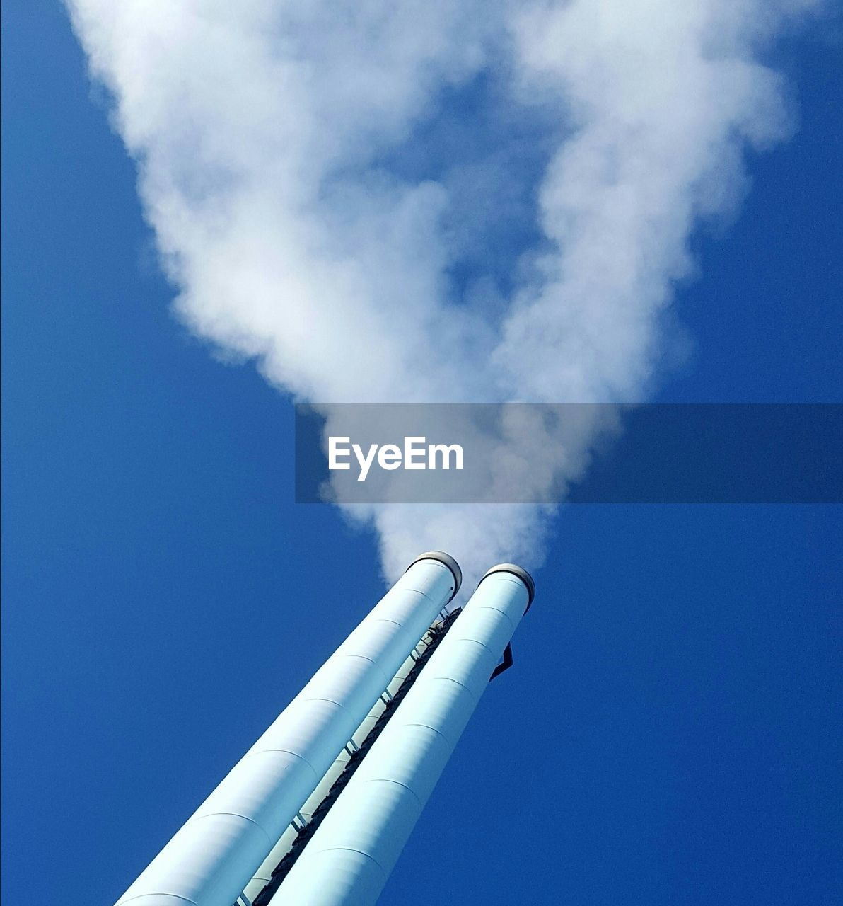 factory, pollution, industry, low angle view, smoke stack, smoke - physical structure, sky, environmental issues, blue, air pollution, emitting, day, building exterior, nature, environmental damage, no people, chimney, environment, built structure, fuel and power generation, outdoors, fumes
