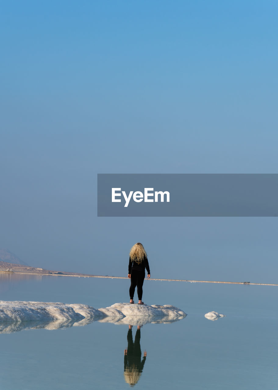 Rear View Of Woman Standing On Salt At Dead Sea Against Blue Sky