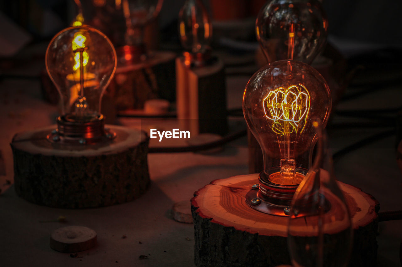 lighting equipment, close-up, indoors, no people, illuminated, focus on foreground, technology, table, electricity, light bulb, glass - material, glowing, transparent, oil lamp, old, retro styled, filament, electric lamp, light, glass, antique