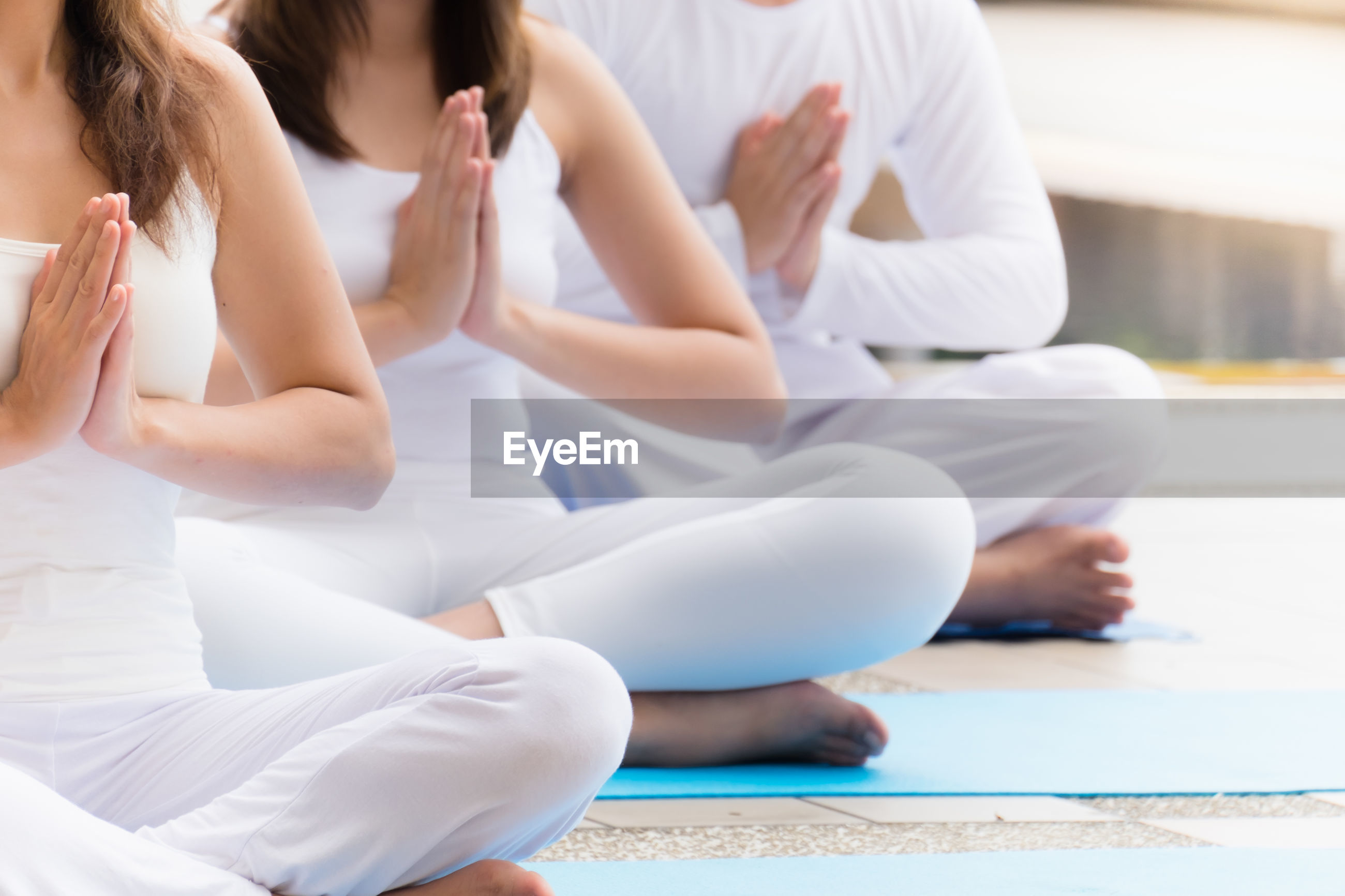Low section of people meditating on floor