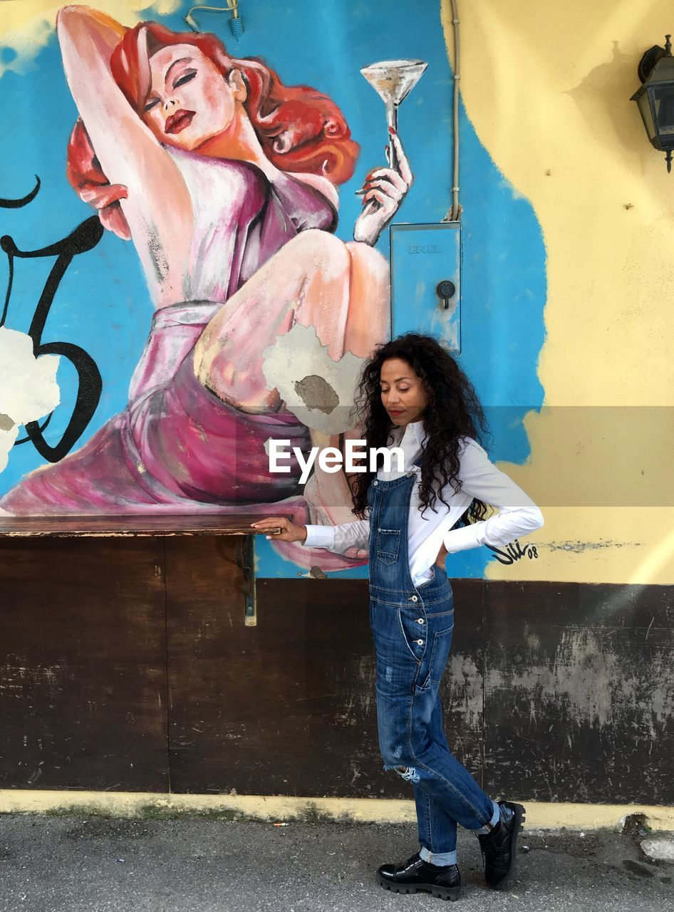 one person, full length, real people, leisure activity, casual clothing, smiling, young adult, happiness, lifestyles, young women, emotion, portrait, front view, creativity, wall - building feature, graffiti, art and craft, looking at camera, hairstyle, hair, beautiful woman, outdoors