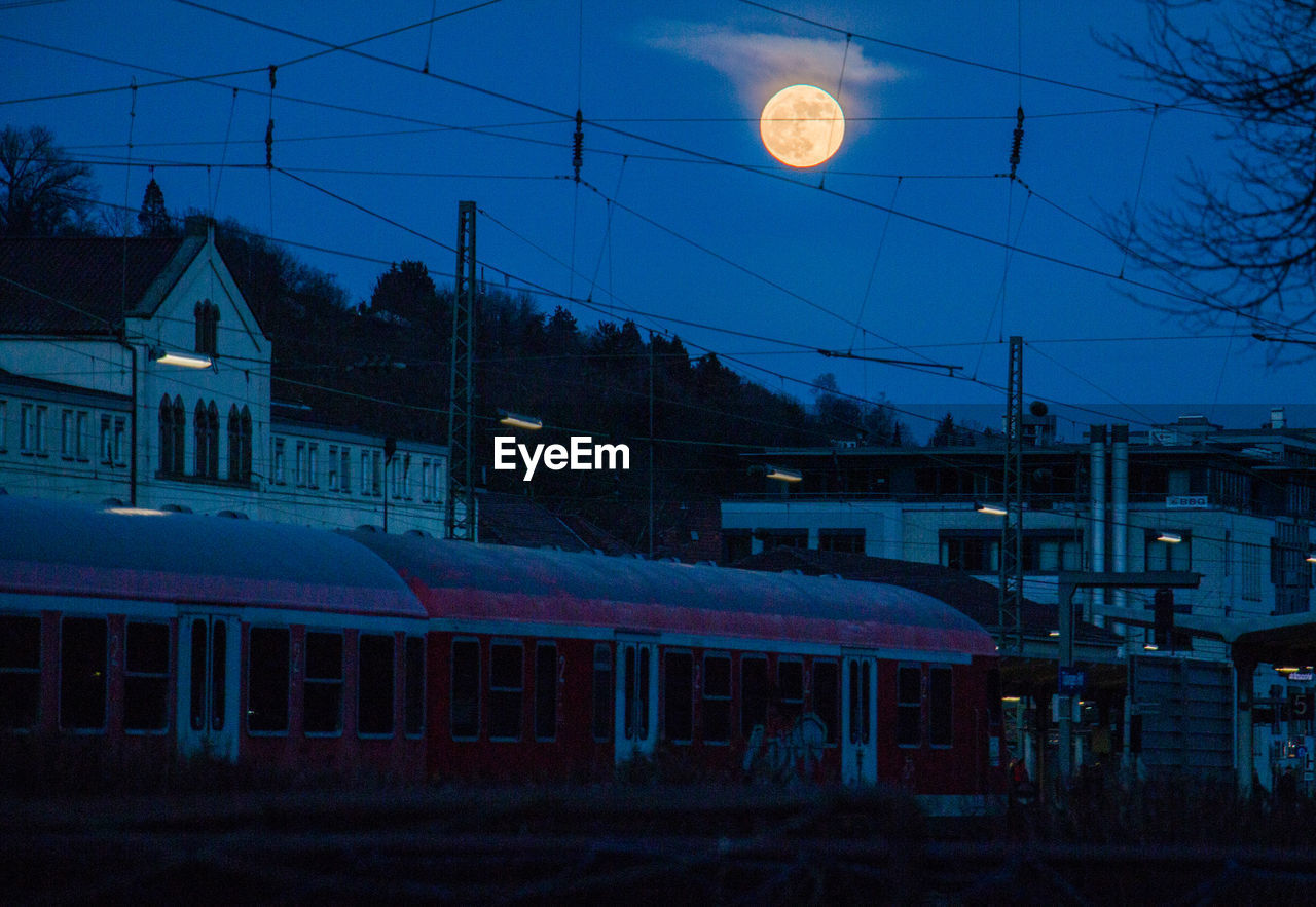 architecture, built structure, building exterior, night, transportation, moon, sky, no people, cable, outdoors, illuminated, railroad track, nature, city