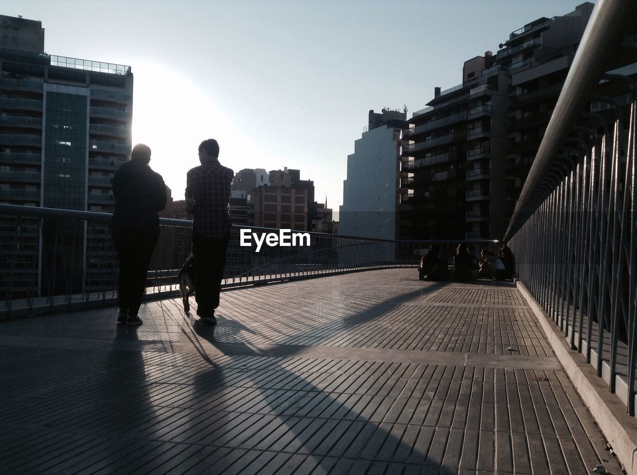 People On Elevated Walkway In City During Sunny Day