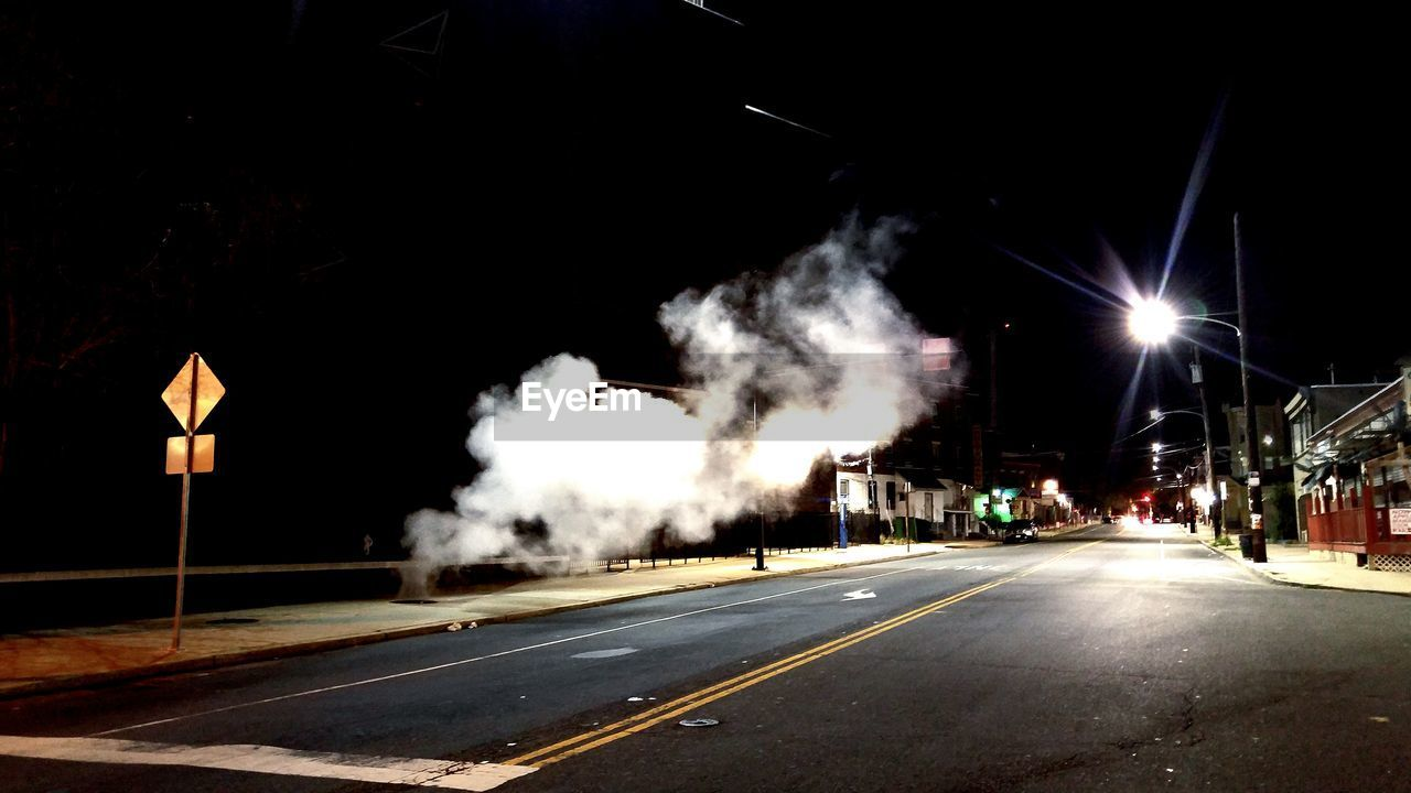 night, transportation, illuminated, smoke - physical structure, road, sky, outdoors, motion, street light, no people