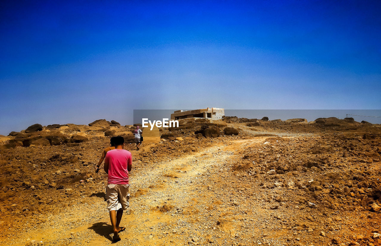 Rear View Of People Walking On Dirt Road Against Blue Sky