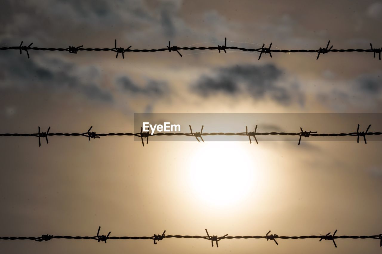 Close-up of silhouette barbed wires against sky during sunset