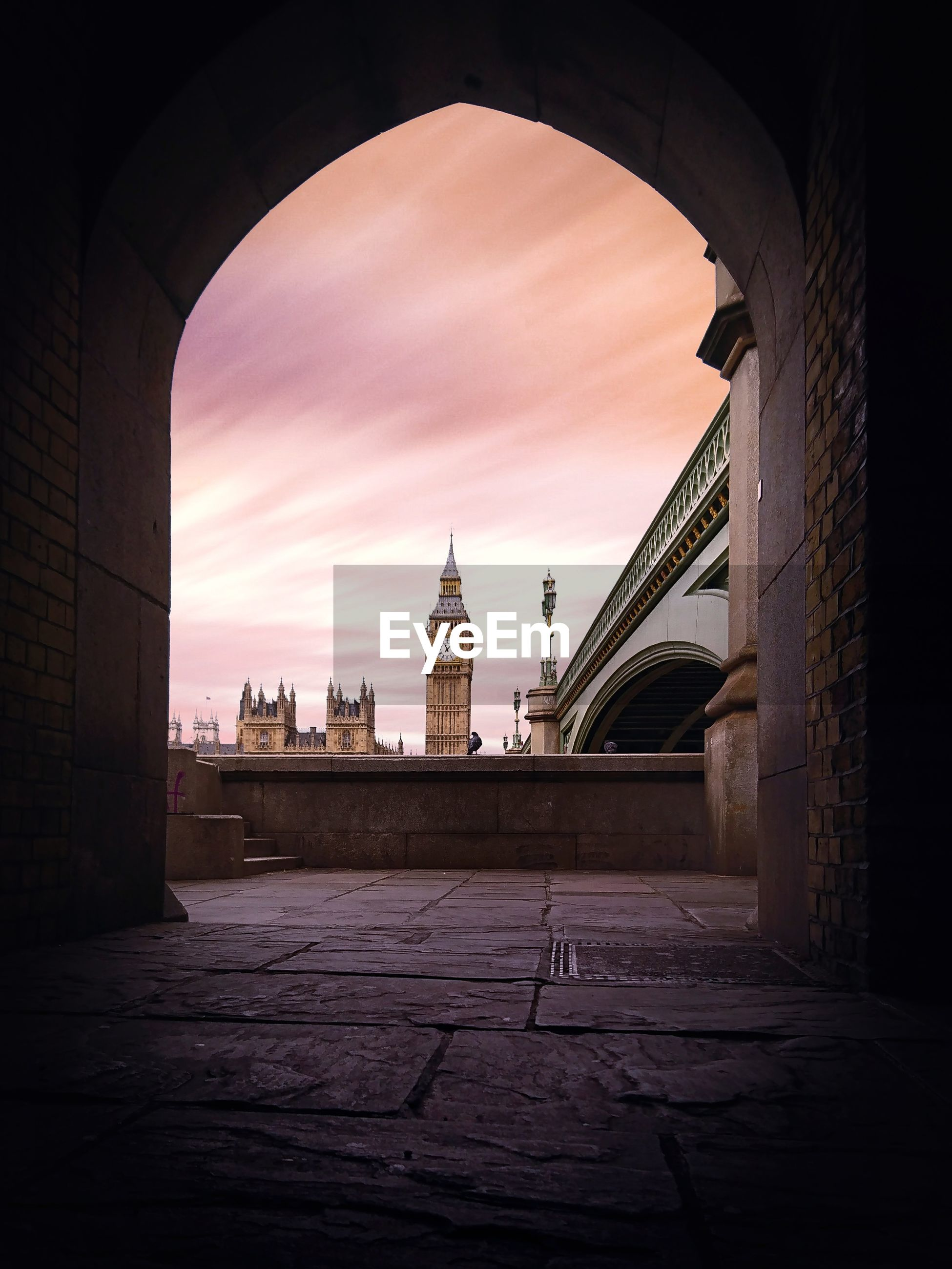 Big ben seen through arch against sky in city during sunset