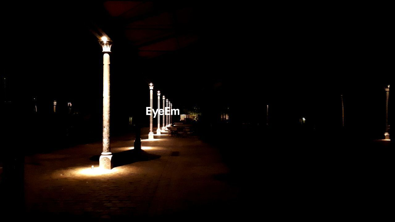 illuminated, night, lighting equipment, architecture, built structure, no people, the way forward, direction, in a row, dark, architectural column, street, outdoors, nature, street light, building exterior, building, glowing, diminishing perspective, city, light, colonnade, electric lamp