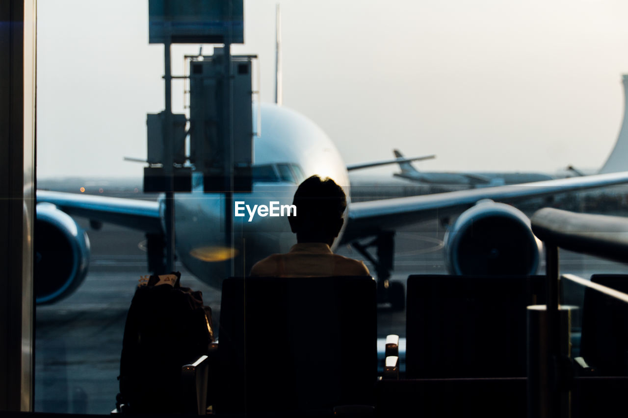 Rear View Of Man Sitting At Airport Lobby Against Airplane