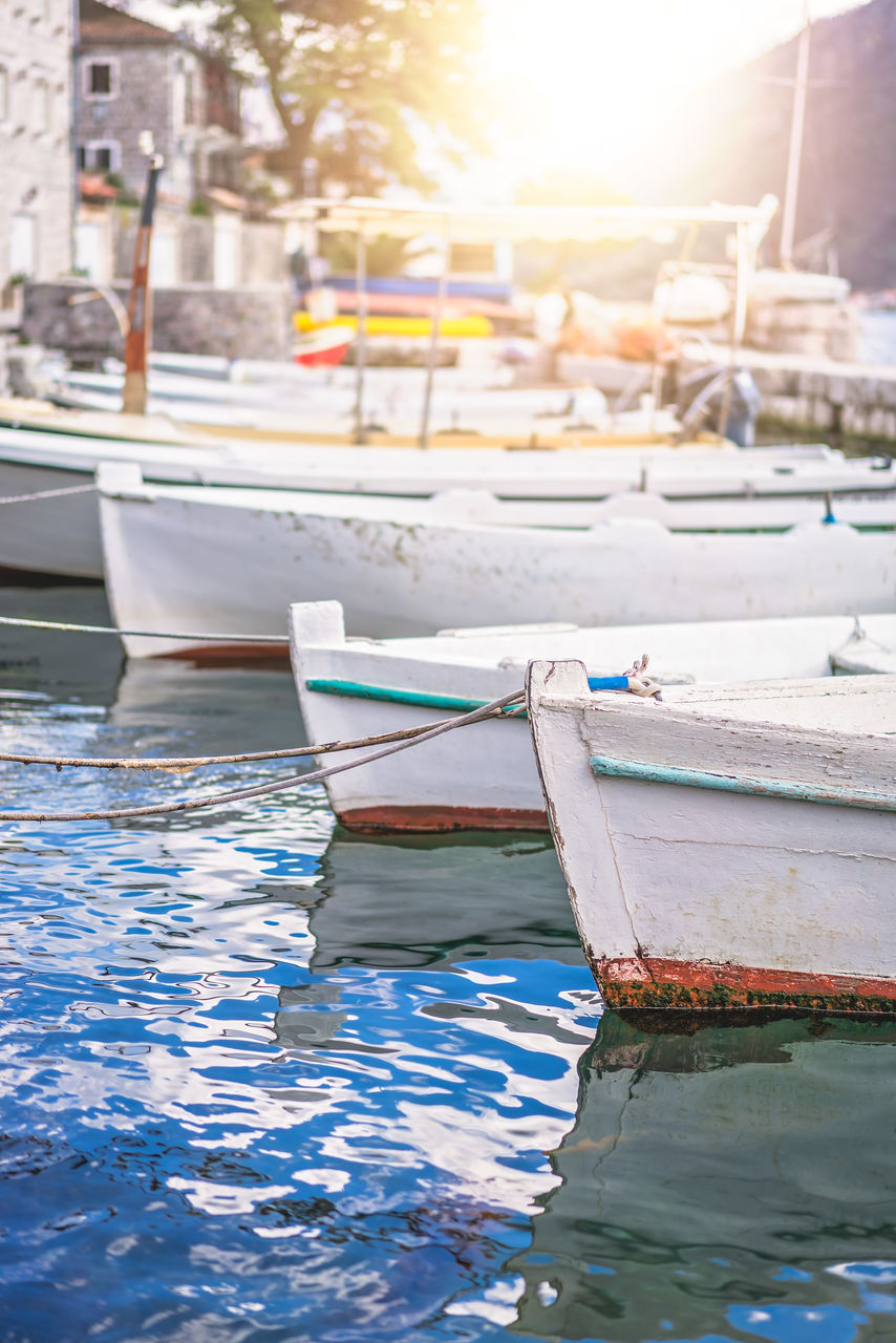 nautical vessel, transportation, mode of transportation, water, moored, no people, nature, day, waterfront, reflection, harbor, outdoors, focus on foreground, sunlight, architecture, rope, lake, rippled, swimming pool, rowboat, fishing boat, sailboat